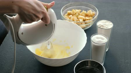charlotte pie : Close-up womans hands with a mixer whisk eggs in a bowl and add sugar. Cooking apple pie. Stock Footage