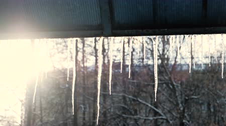 paving : Icicles hang from a roof in spring thaw. Stock Footage