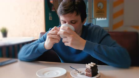caloric : Young man drink a tea in cafe.