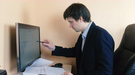 compares : Man works at a computer. Compares graphics on the screen and on paper.