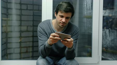 addiktív : Man is playing games on a mobile phone sitting on windowsill. Stock mozgókép