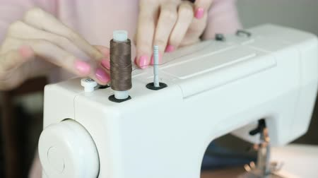 портной : Seamstress rewinds the thread on the bobbin on the sewing machine. Стоковые видеозаписи