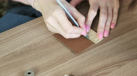 diligence : Seamstress measures segments on leather fabric with pencil and ruler, womans hands close-up. Stock Footage
