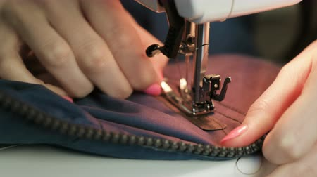 zíper : Close-up of Seamstress sews to blue jacket leather inserts on white sewing mashine.