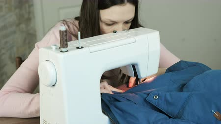 zíper : Young woman sews blue jacket on white sewing mashine. Look at her work.