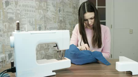 entusiasmo : Young woman sewn the sleeve of a blue jacket. Near on the table sewing machine.