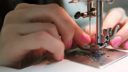 шить : Close-up of the womans hand is inserted into the needle thread sewing machine.