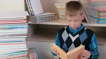 tome : Seven-year-old boy attentively reads the book sitting among books and sneezes.