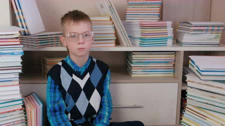 ansiklopedi : Tired seven-year-old boy with glasses sitting on the floor among the books.