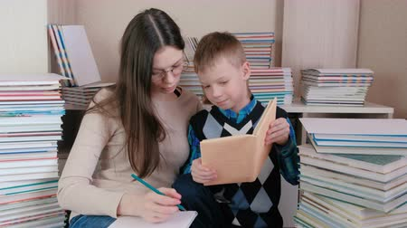 tome : Mom and son read a book together. Mom in glasses writes something in a notebook.