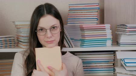 alfabetização : Young brunette woman in glasses hugging a book looking at the camera sitting among books.