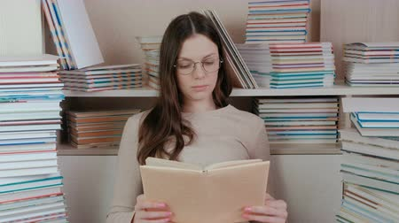 alfabetização : Young brunette woman in glasses reading a book. Sitting among the books