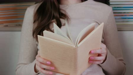 читатель : Unrecognizable young brunette woman looking through a book.