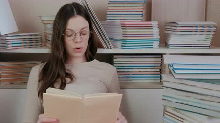 tome : Young brunette woman in glasses reads a book aloud while sitting among.
