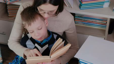 alfabetização : Mother teaches son to read. Family reading a book together.