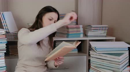 ansiklopedi : Young brunette woman wearing glasses read book sitting on the floor among the books. Stok Video