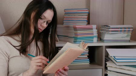 tome : Young brunette woman wearing glasses read book making notes with a pencil.