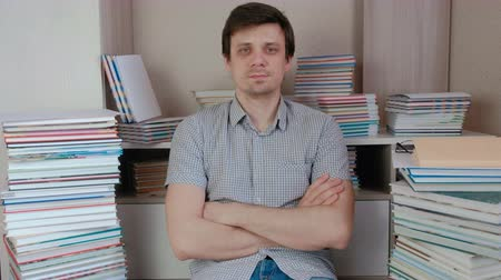 ansiklopedi : Young brunet man sitting among the books and look at camera.