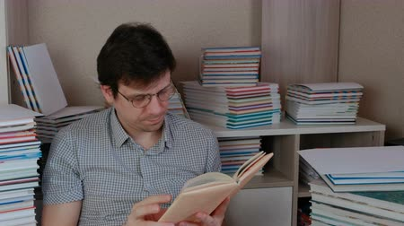 taslakkitabım : Young brunet man puts on his glasses and reads a book sitting among books. Stok Video