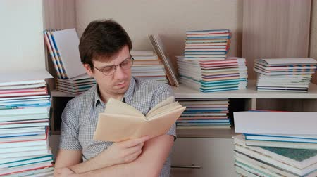 verificador : Young brunet man in glasses reads a book and thinks sitting among books.