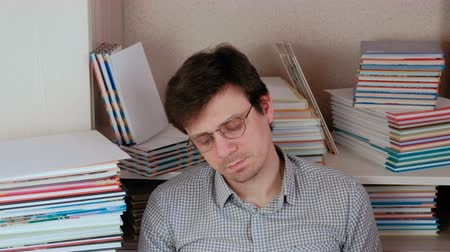 ansiklopedi : Young tired brunet man sitting among the books.