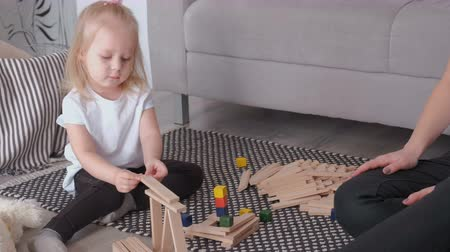 logic : Little charming blond girl playing wood blocks with her mom sitting near the sofa.