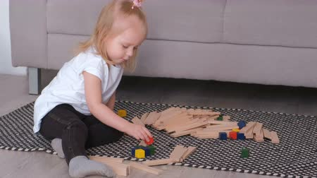 logic : Little charming blond girl building wood blocks sitting near the sofa. Stock Footage