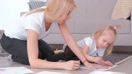 ipuçları : Little charming blond girl painting wraps her moms hand around with felt-pen sitting near the sofa.