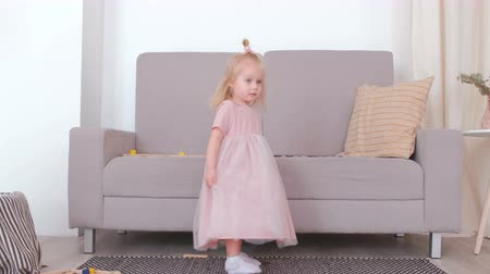 pillow block : Little charming happy girl revolve in beautiful pink dress.