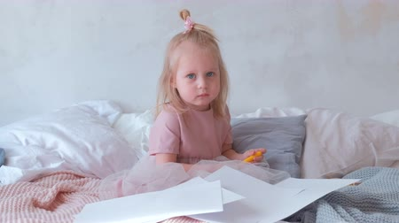 unidentified : Little charming blond girl in pink dress holding a felt-pens and sitting on bed among paper.