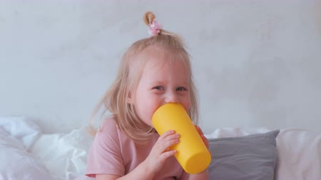 kořist : Little charming blond girl in pink dress plays with yellow plastic cup with her mom. Dostupné videozáznamy