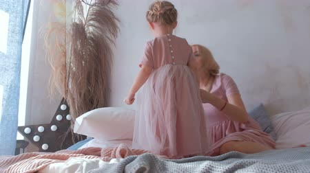 minder : Young attractive blond mom plays with her little charming daughter in pink dresses laying in bed. Stok Video