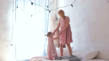 cobertor : Young attractive blond mom jumping on bed with her little charming daughter in pink dresses.