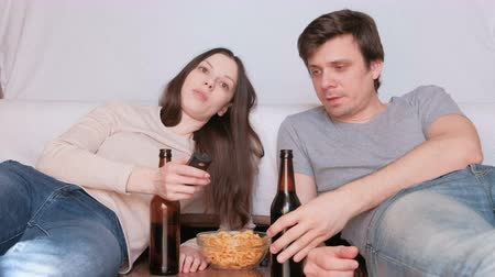 switching : Couple of young man and woman eating chips drinking beer and watching TV, switching channel. Talking and smiling.