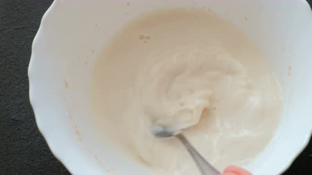 padeiro : Mixing the yeast with the milk with spoon closeup. Yeast dissolves in milk. Preparation of yeast dough. Stock Footage