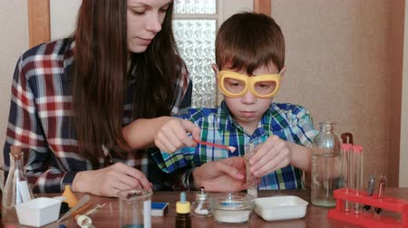 experiência : Chemistry experiments at home. Mom and son make a chemical reaction with the release of gas in the test tube.
