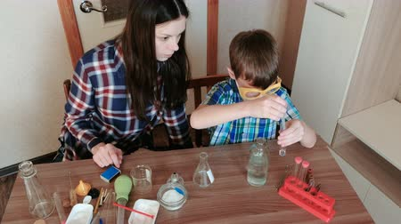 diligence : Chemistry experiments at home. Boy pours water from the bottle into the test tube using a pipette.