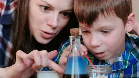 flasks : Chemistry experiments at home. Mom and son make a chemical reaction with the release of gas in the flask. Stock Footage