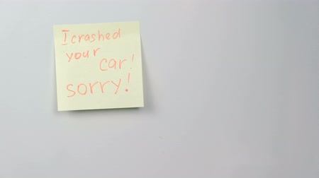 клейкий : Closeup yellow sticker paper sheet with words i crashed your car, sorry on refrigerator.