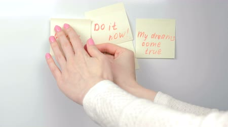 saying : Closeup womans hands stick yellow sticker paper sheets with motivation phrases on a white board.