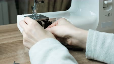 diligence : Close-up female hands disassemble the sewing machine and clean it from dust with a brush.