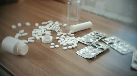 codeine : Round white tablets and oval pills on the table with empty boxes and blisters.