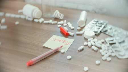 aşırı doz : The inscription on the sticker - sorry - amongst the scattered pills on the table