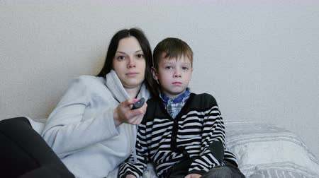 watch tv : Watching TV lying on the couch. Mom and son watch TV together and smile. Mom switches channels. Stock Footage
