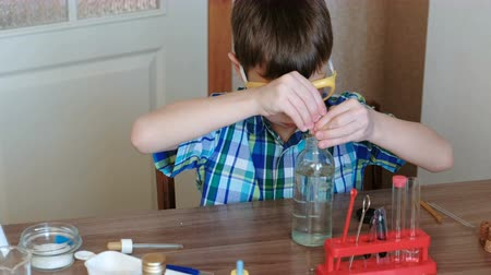 diligence : Experiments on chemistry at home. Boy takes a bottle of water and pours water into the tube with a pipette. Side view. Stock Footage