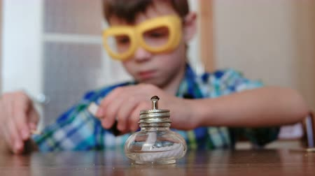 gently : Experiments on chemistry at home. Boy sets the burning alcohol lamp on fire with a match.