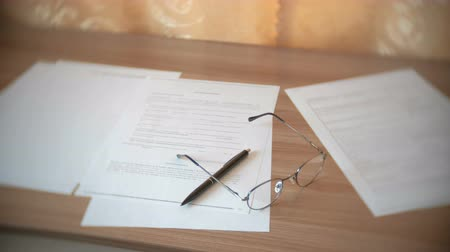 burocracia : Glasses, papers documents and pen on the table. Stock Footage