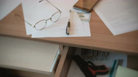 cinayet : Testament, pen, glasses and money on the table, and gun in a table drawer. Stok Video