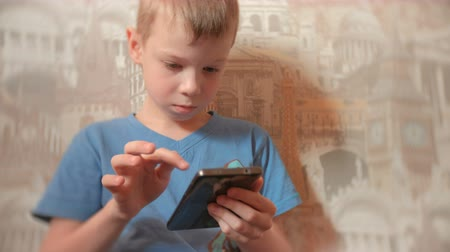 boyish : Seven-year-old boy browsing internet on his mobile phone with serious face.
