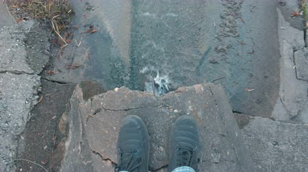 gushing : Man is looking on water pollution discharge from the drain. Closeup mans legs.